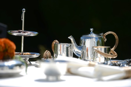 high tea: Table set for an English high tea, or afternoon tea, outside with silver teapot and linen tablecloth
