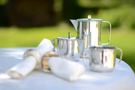 napkin ring: Luxury silver coffee pot on a linen covered table outside in summer.