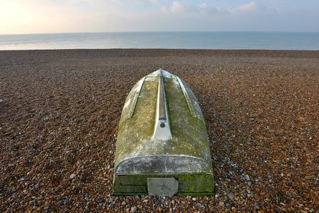 stoney: Upside down fishing boat on shingle beach