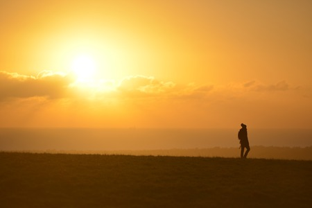 Lone walker on the South Downs at sunset