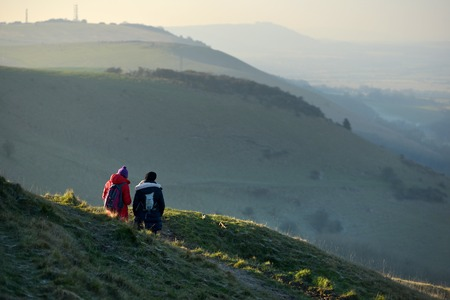 Two walkers looking at the view from Devils Dyke in the South Downs National Park, Sussex Stock Photo