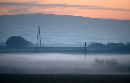 Electricity pylons at dusk with low lying mist