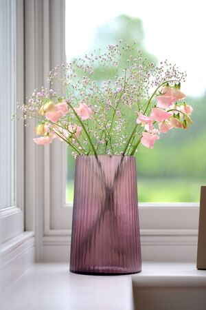 Pink cut glass vase with flowers in a room setting Stock Photo