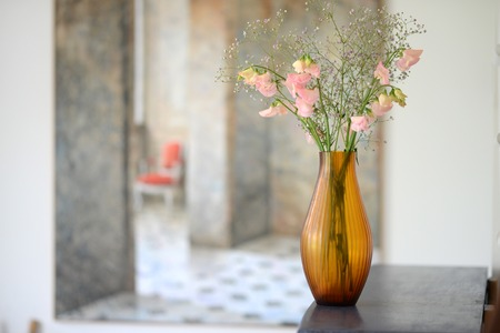 Amber glass fluted vase with flowers in a room