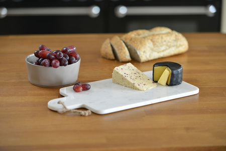 tabla de quesos: White marble cheese board in a kitchen with cheese and grapes
