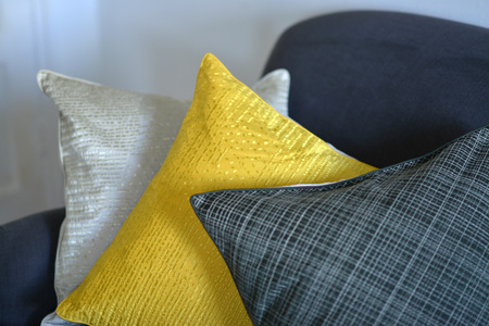Three textured cushions on a greyblue couch