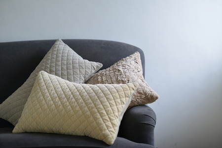padding: Three textured cushions on a greyblue couch