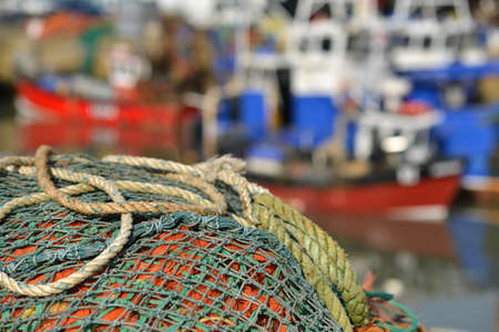 Fishing nets on a jetty with fishing boats the background