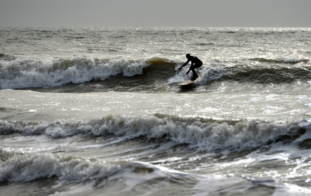 Surfer surfing during a grey winter day in britain Stock Photo