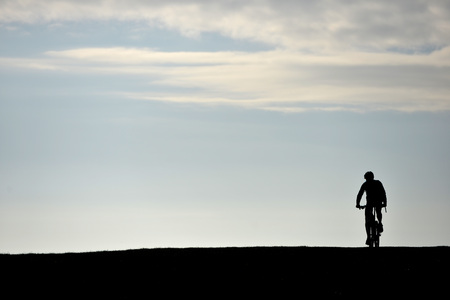 Man on a mountain bike silhouetted by morning sky