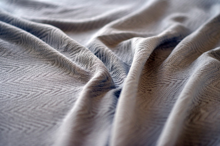 Neutral coloured textured bedspread  throw on a bed Stock Photo