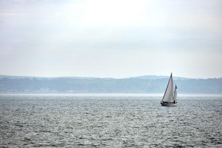 Yacht sailing on a grey overcast day near Portsmouth, UK