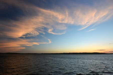 Thin clouds over the sea illuminated at sunset Stock Photo