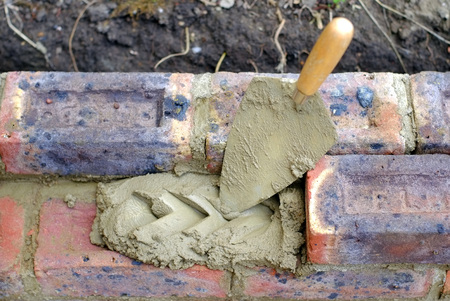 Bricklayers trowel and mortar on a construction site