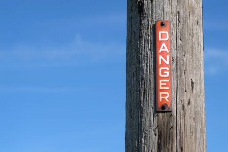 Red and white danger sign on a pylon