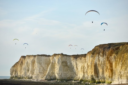 Paragliders over chalk sea cliffs in Newhaven, East Sussex, UK