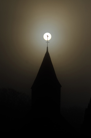 Bird perched on top of a church spire in front of the sun