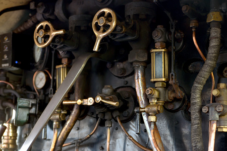 Control levers and valves inside a steam train cab