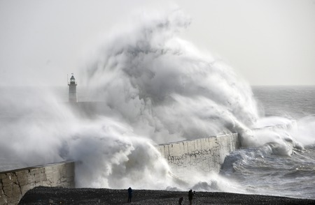 Huge waves crash against a sea wall and lighthouse during a winter storm, Newhaven, East Sussex Stock Photo