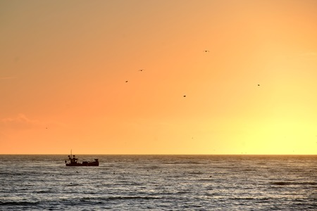 Fishing boat on a calm sea at sunset