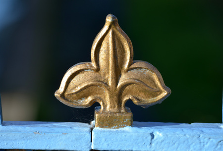 Golden finial fleur de lys on a blue railing