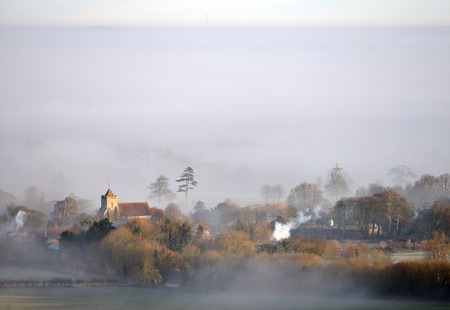 Mist surrounding the village church in Firle, East Sussex Stock Photo