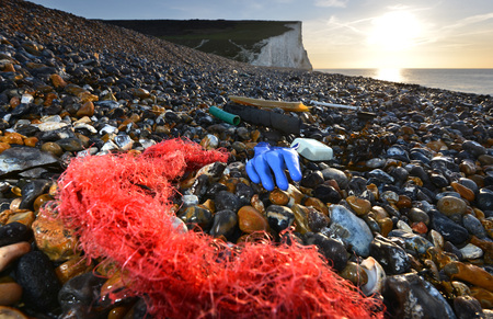 Plastic washed up Cuckmere Haven beach, showing the Seven Sisters Chalk clffs, East Sussex