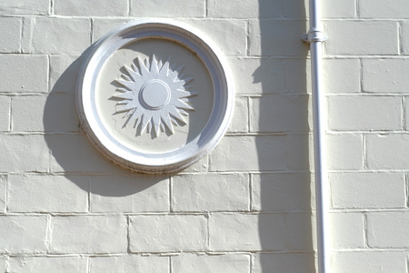 Decorative plaster panel on the outside of a painted brick wall