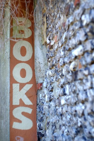 Book sign on an old flint wall Stockfoto