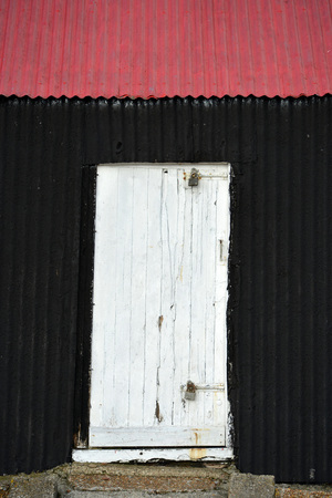Corrugated iron building painted red and black Фото со стока