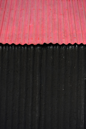 Corrugated iron building painted red and black Standard-Bild - 119243799