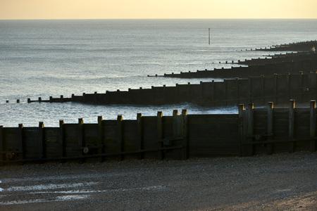Wooden groynes on a shingle beach to prevent coastal erosion Standard-Bild - 119354512