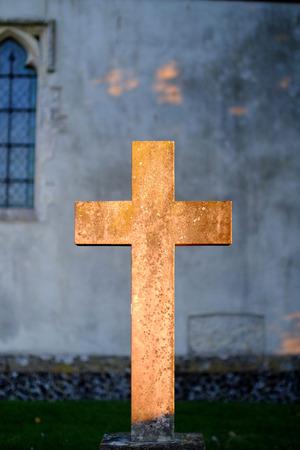 Golden light illuminating a church crucifix 写真素材