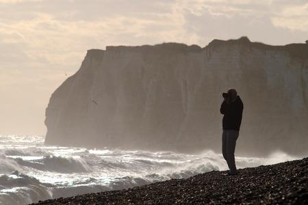 Man photographing stormy seas near sheer cliffs