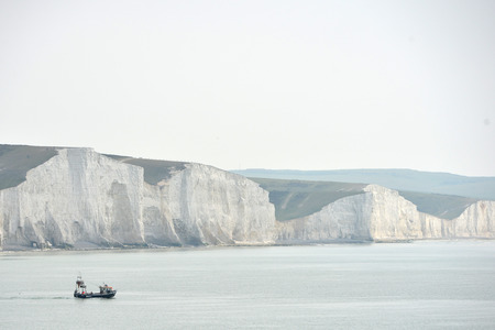 Small fishing boat in the English Channel with chalk cliffs in the background, East Sussex Standard-Bild - 122334781