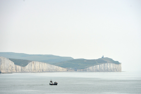 Small fishing boat in the English Channel with chalk cliffs in the background, East Sussex Stock Photo