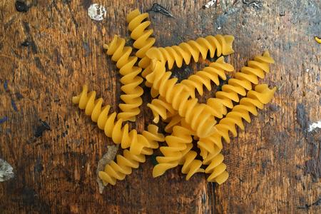 Dry fusilli pasta on a wooden board