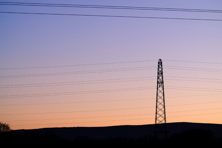 Electricity pylons making geometric shapes at sunset.