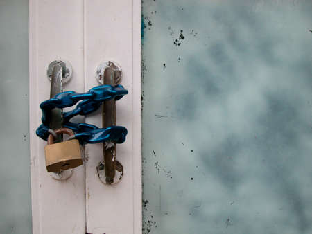 Old white glass door closed with blue chain and padlock photo