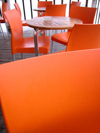 Orange plastic chairs and wood tables in an outdoor bar Stock Photo - 4927919