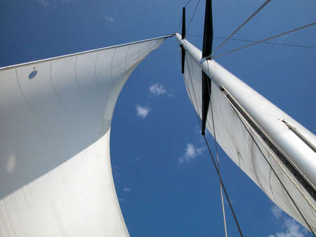 A view looking upwards at the mast, sail and rigging of a yacht underway