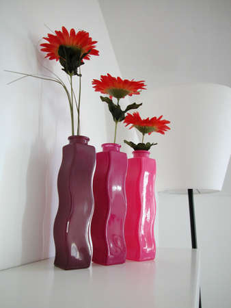 Three blooms in different colours glass vases