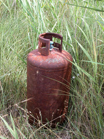 Rusted old gas bottle abandoned in the meadow