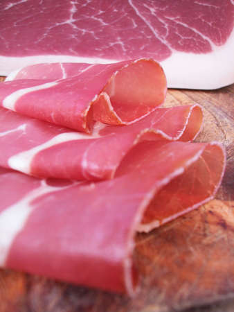 trencher: Closeup of sliced ham, typical italian prosciutto on wood trencher