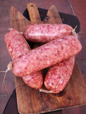 Italian typical spiced sausage cotechino on wood trencher