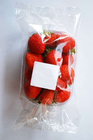 Strawberries in plastic box with free space on white label, white background photo