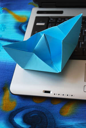 Blue paper boat sailing on laptop, vacation concept, internet surfing concept Stock Photo - 5148478