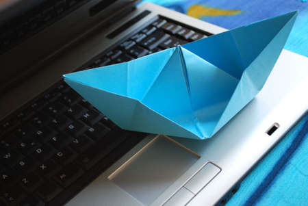 Blue paper boat sailing on laptop, vacation concept, internet surfing concept