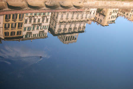 Ancient houses reflecting into the water on Arno river, Florence, Italy