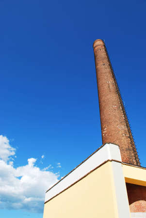 Ancient industrial brick chimney against blue sky photo
